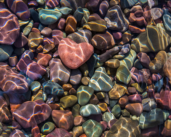 Touching heart shape rock amidst colorful stones in lake