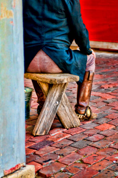 Red Brick Cowboy in Boots on Bench