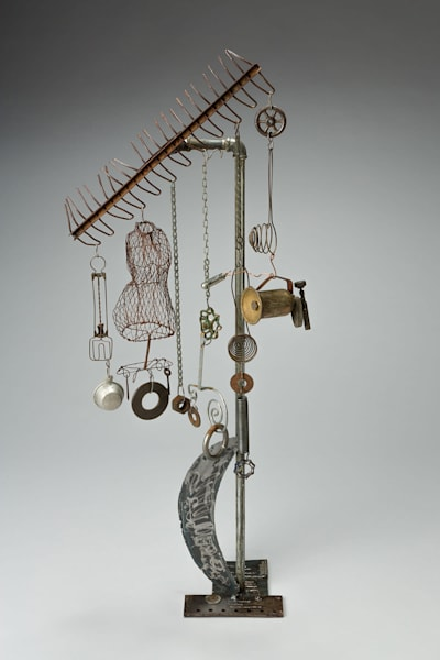 "Salvaged metal sculpture, ""Moon's Influence"" is composed of welded metals, found objects with dangling elements that can move with wind if positioned so."
