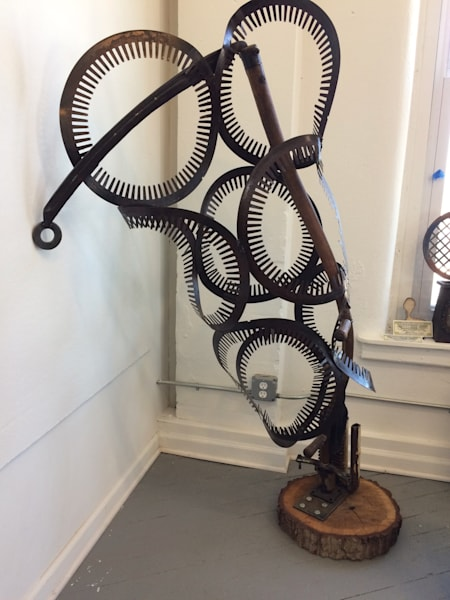 """Death Swallowed Up By Life"" recycled sculpture made of  wood, wooden vintage scythe and radiant disks measures 66"" high x 25"" wide x 28"" deep"
