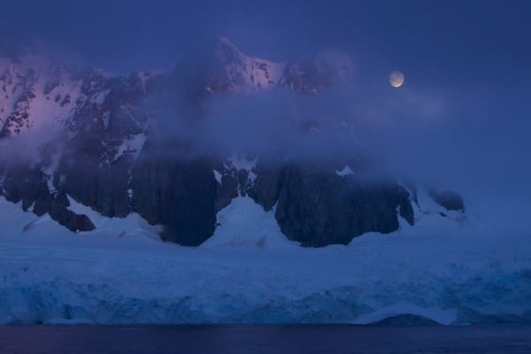 The moon comes out between clouds over peaks along the vicinity of the Lemaire Channel, Antarctica