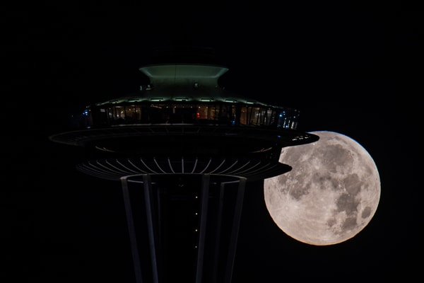 Full moon setting behind Space Needle