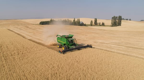 Aerial view of a John Deere combine cutting wheat on a sunny afternoon, Spokane County, Washington
