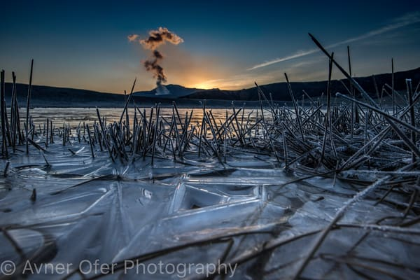Sunrise from frozen lake, looking at smoking Aso volcano, Japan