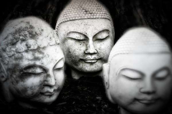 a trio of black and white buddha heads