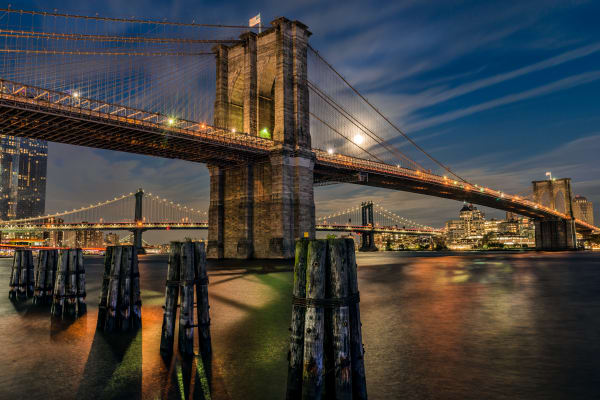 Moon rising above Brooklyn Bridge at twilight
