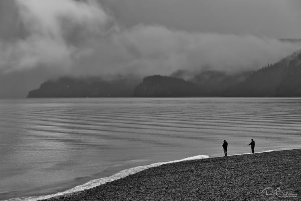 Two fisherman fishing for salmon in Resurrection Bay along Lowell Point in Seward in morning fog on the Kenai Peninsula in Southcentral Alaska. Summer.