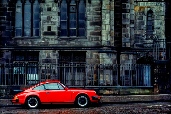A red Porche 911, in front of centuries old grey  stone structure,  Edinburgh, Scotland