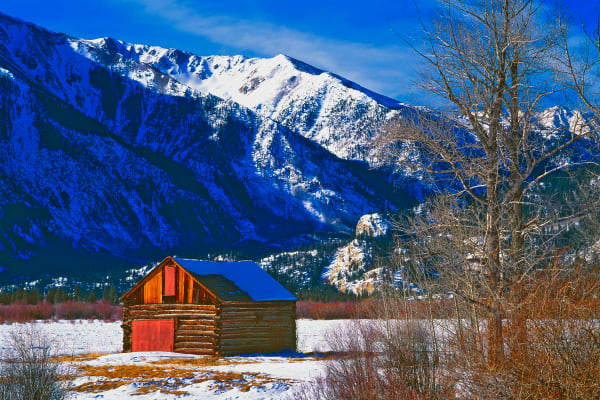 Old log barn in Rocky Mountains, winter.
