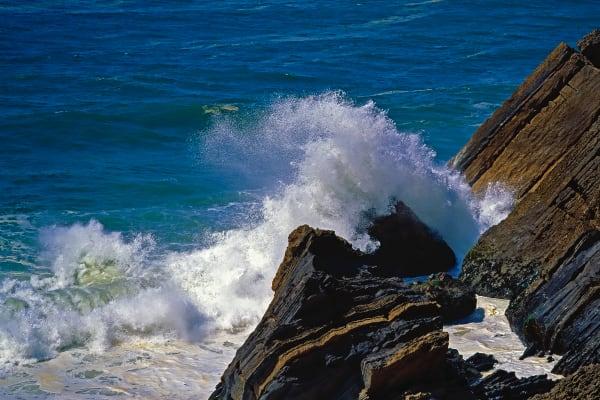 Atlantic Ocean waves break on a rugged Portugeuse coastline.