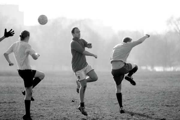 Whimsical B&W image of male soccer players in morning mist, Hyde Park, London