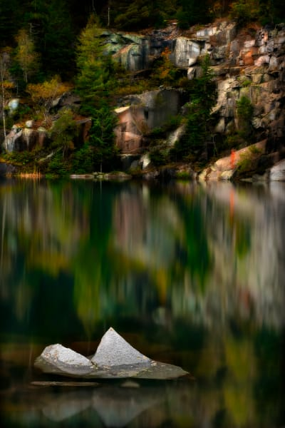 Jagged rock in quarry pond.