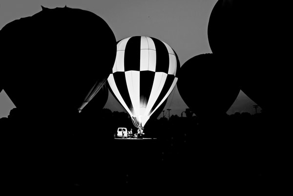 Black and white photograph of a hot air balloon glow festival