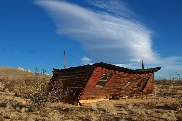a weathered and wind blown shack about to falll down on hwy 395 in California