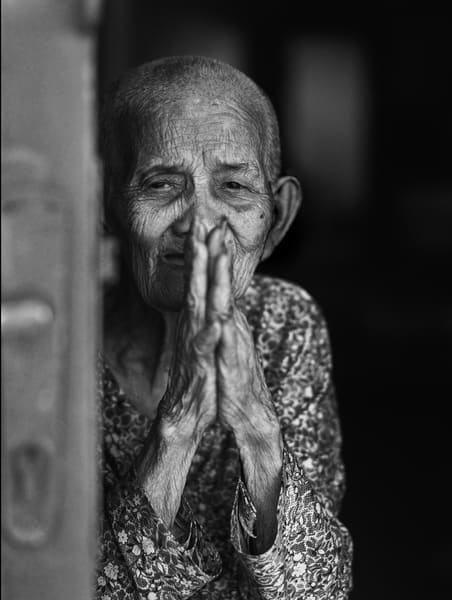 An unscripted black and white street portrait of a woman offering praying hands as a greeting.