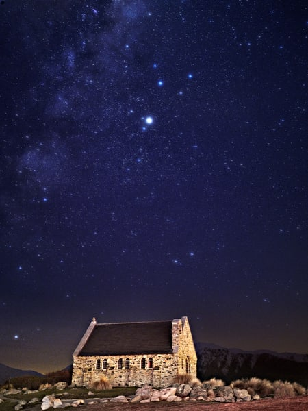Beautiful photograph of a stone church under the stars