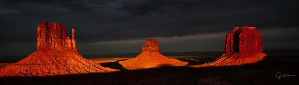 Monument Valley during a great sunset with dark clouds enhancing the Mittens.