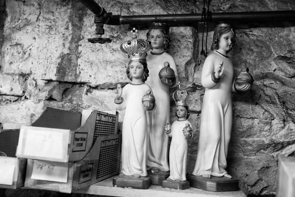A group of small religious statues, some with crowns, in Martin's workshop. he statues are commonly supplied with simple robes coast as part of the statue; fabric robes are added later.