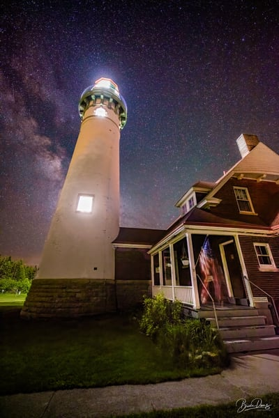The Suel Choix Pointe Lighthouse with the milky Way and American Flag