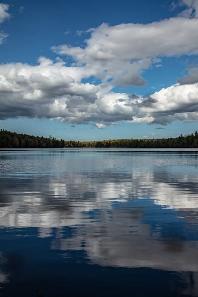 Late afternoon clouds are reflected in the mirrored waters of High Lake in Michigan's Sylvania Wilderness.