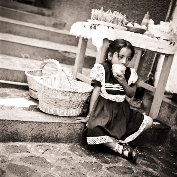 A young vendor girl is daydraming in rural Mexico.