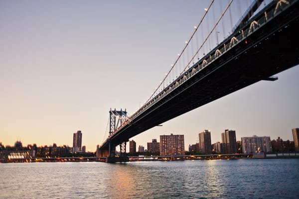 Manhattan Bridge spanning across the waters into Manhattan in sunset sky.