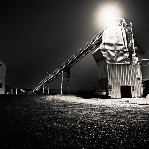 Night photo of an industrial mill with light shining from the top.