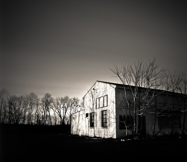 Night photo of a rundown building with dramiatic clouds and trees.