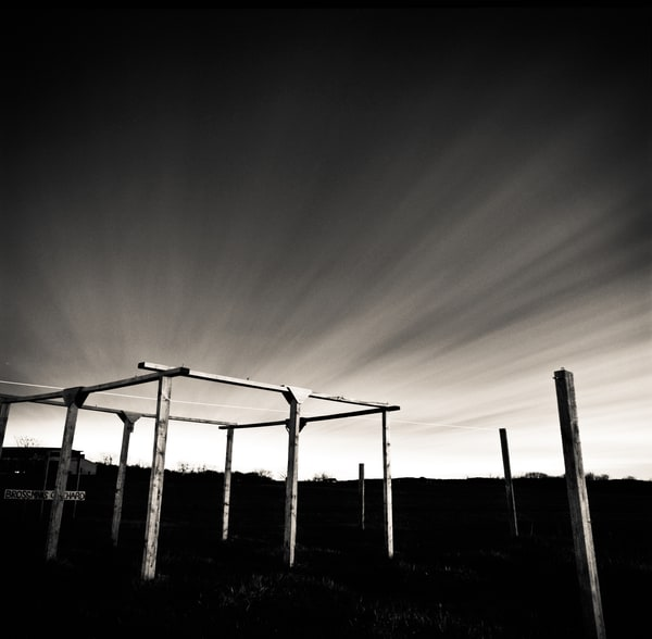 Night photo of wooden framing posts with dramatic sky in the background.