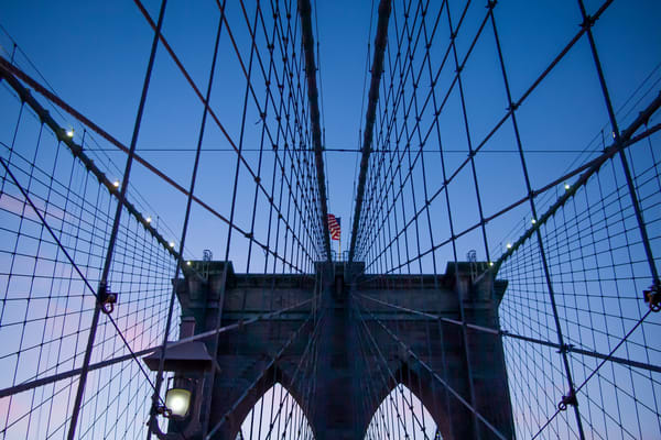 A tower and cables of the Brooklyn Bridge from the east, just after sunset.
