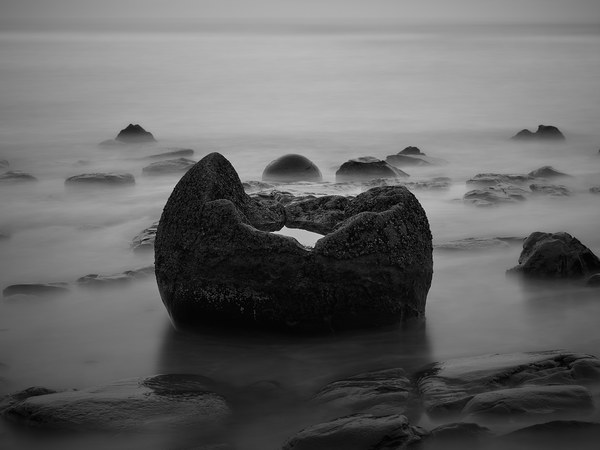 A limited edition, black and white, landscape photograph of a Moeraki Boulder lying on the beach with a pool of water gathered in its center.