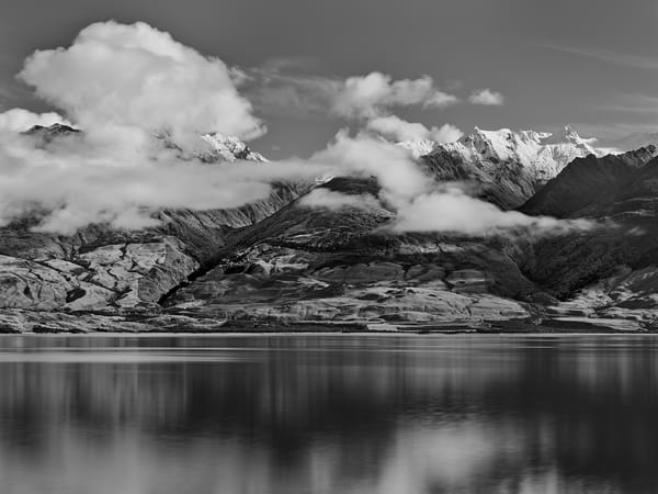 A limited edition, classic black and white mountain landscape photograph with dramatic clouds overhead.