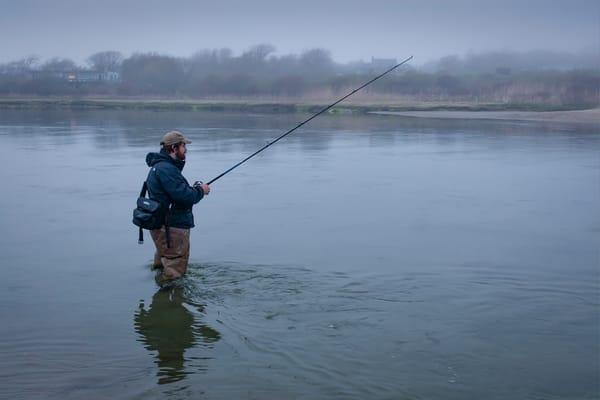 A man fishing in the fog at the entrance to the Narrow River, Narragansett, Rhode Island.