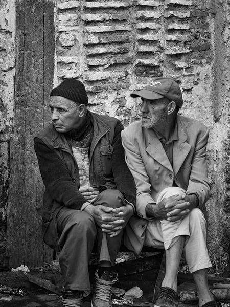 Black and White portrait of two men sitting together exhibiting similar poses