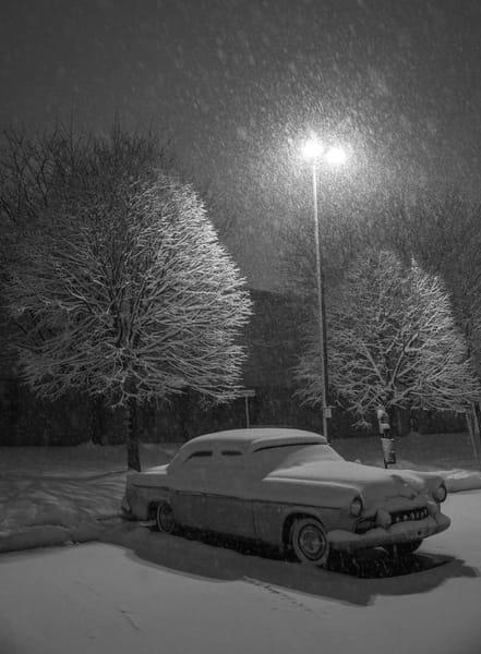 Snow fall covers an antique car