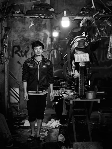 Timeless black and white street portrait of a bike repair shop owner in Vietnam.
