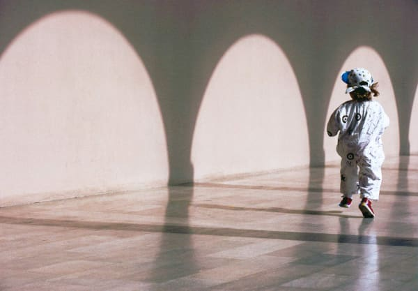 Two year old girl running in the colonnade shadows of the Ringling Museum, Sarasota, Florida