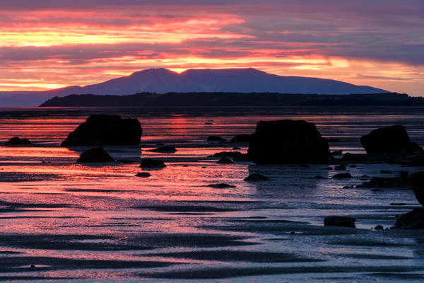 Sunset over Mt. Susitna -- aka: Sleeping Lady -- and mudflats of Turnagain Arm with rocks at low tide.  Summer   Anchorage, Alaska   Copyright Jeff Schultz / SchultzPhoto.com