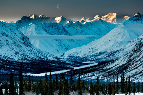 Winter landscape of snow and spruce tree forest with fog and Chugach Mountains and South Fork Matanuska River valley in the Glacier View area of southcentral, Alaska as moon rises