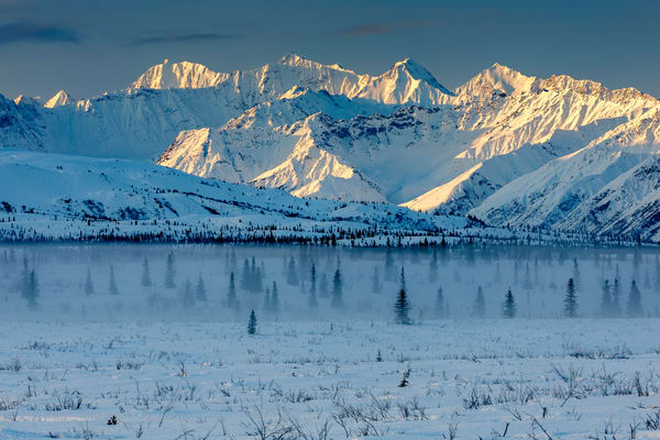 Winter landscape of snow and spruce tree forest with fog and Chugach Mountains and valley in the Glacier View area of southcentral, Alaska