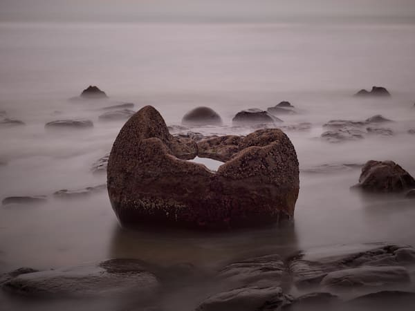 A long exposure landscape photograph of a partially submerged boulder on Moeraki beach with a pool of water in the center.