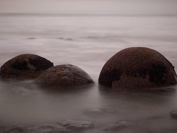A tranquil long exposure landscape photograph of three boulders lying in a mist on a beach.