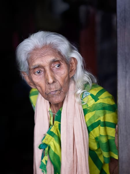 An authentic street portrait of a woman in a doorway.