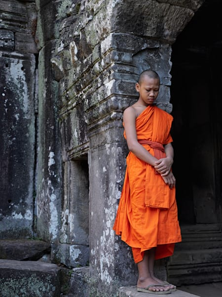 A limited edition framed print of a young devotee pausing amongst the ruins of a temple in Cambodia.