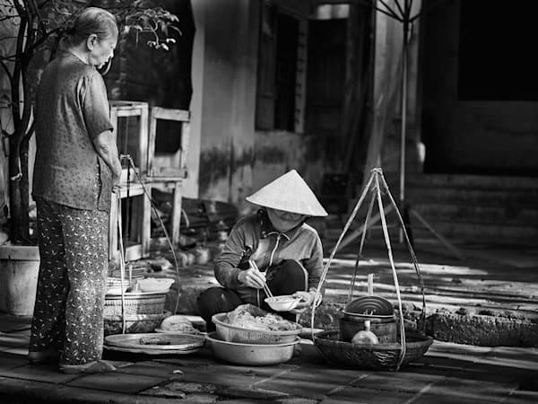 A timeless black and white street photograph of a street food vendor serving a customer on an idyllic street in Siem Reap, Cambodia.