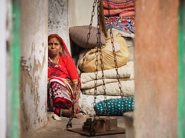 A candid street portrait of a colorful older woman sitting in her home.