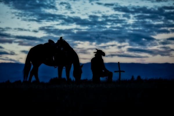Silhouette of Horse and Wrangler Bowing to Cross