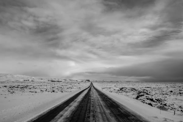 Dramatic black and white photo of a long, empty highway in Iceland during winter