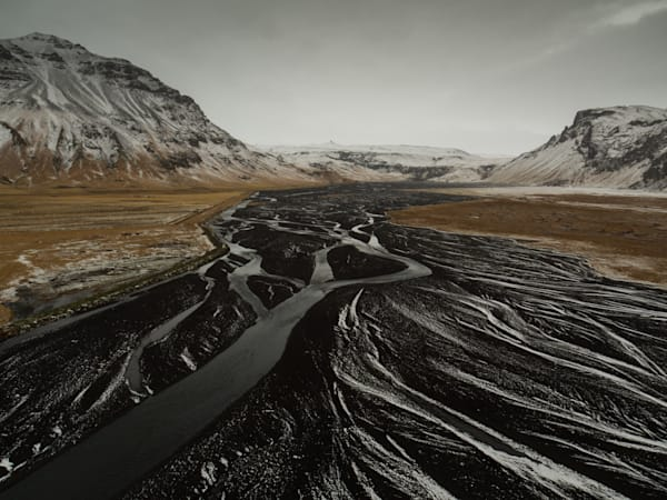 Riverbed made from black volcanic sand flows away from snow covered mountains in Iceland