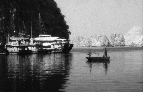 boys fishing in a canoe Ha Long Bay limestone tower